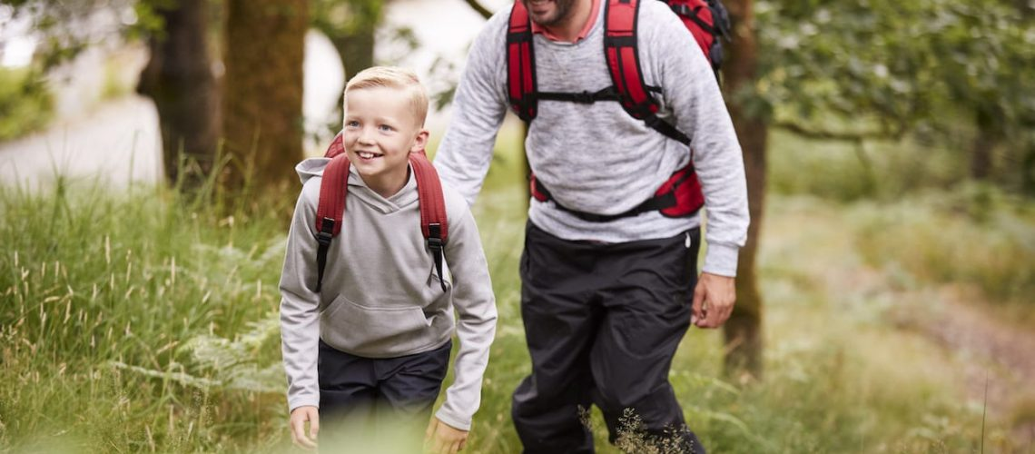 Pre-teen boy and his father hiking in a forest, selective focus