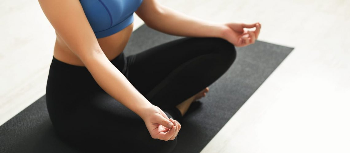 Fitness, unrecognizable woman yoga relax meditation in lotus pose in gym. Young slim girl making exercise.