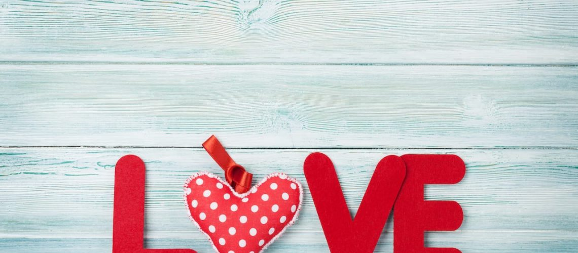 Valentines day greeting card with heart and love word over wooden background. With space for your greetings